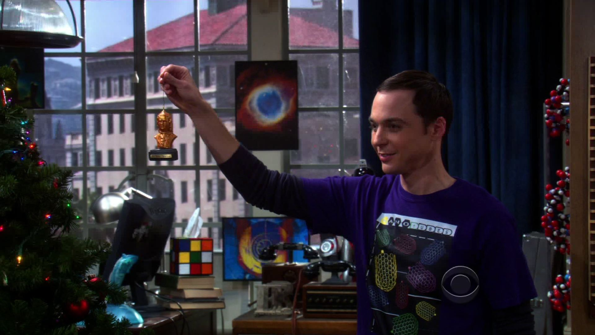 Sheldon holding a bust of Sir Isaac Newton