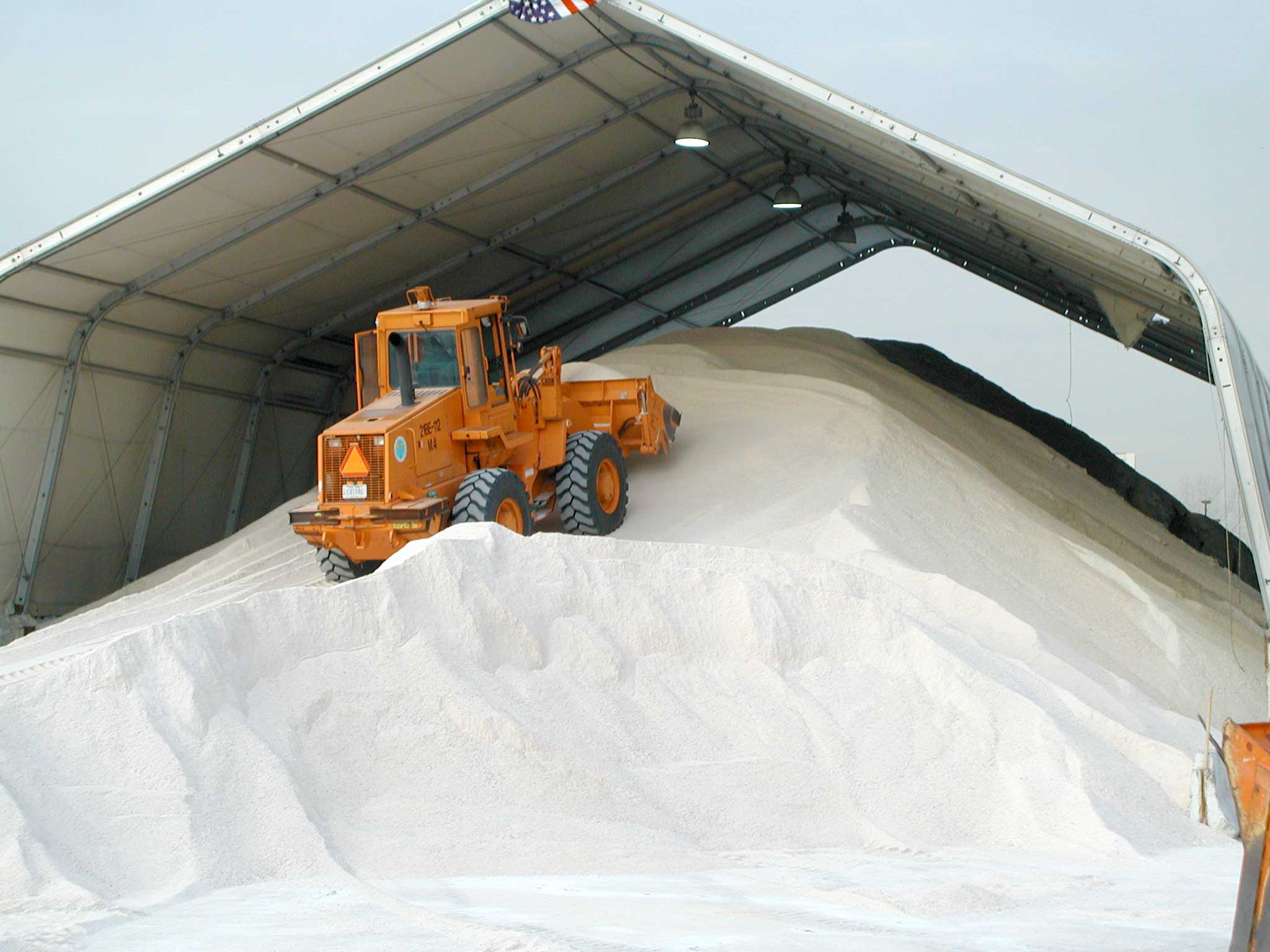 A front end loader driving up a pile of salt in a municipal storage facility