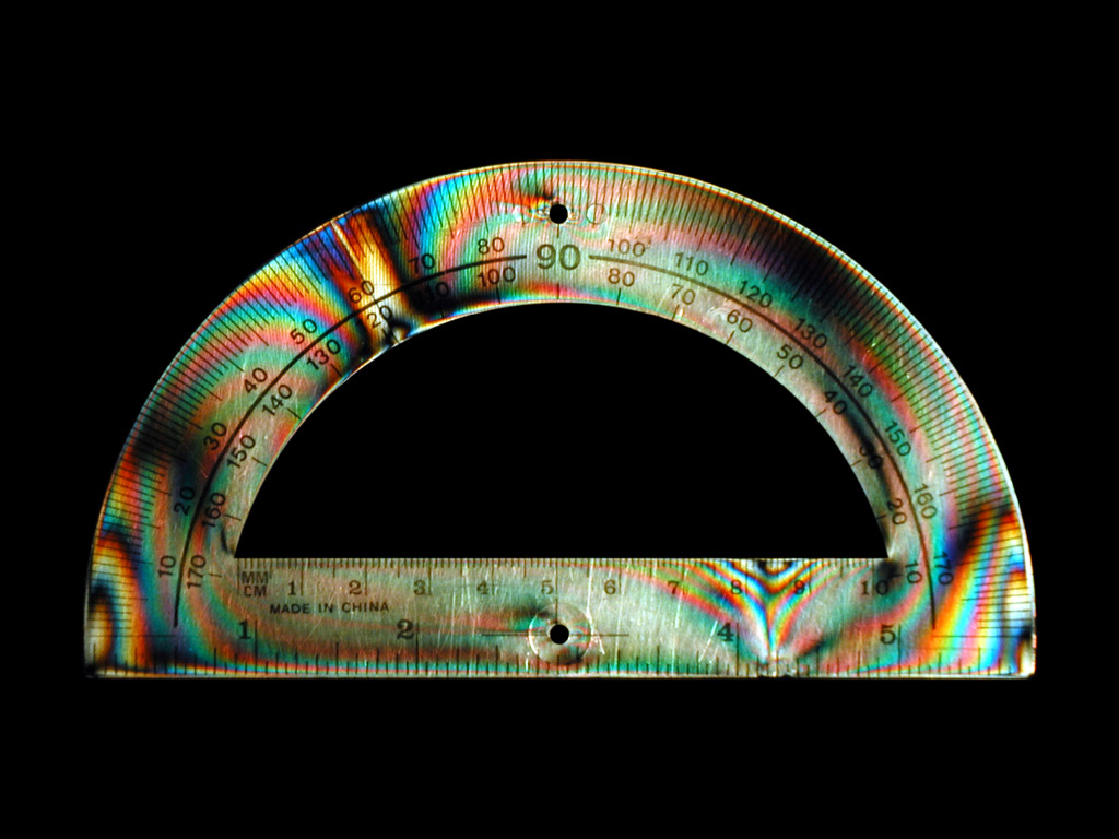 Photo of a protractor in polarized light showing strain at two locations