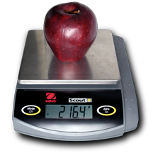 Red delicious apple on an electronic balance reading 216.4 grams